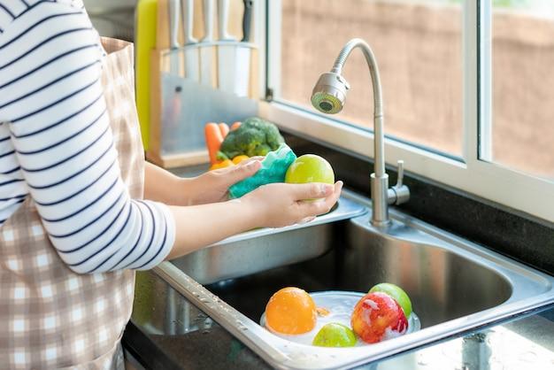 台所の流しの上でリンゴや他の果物を洗う