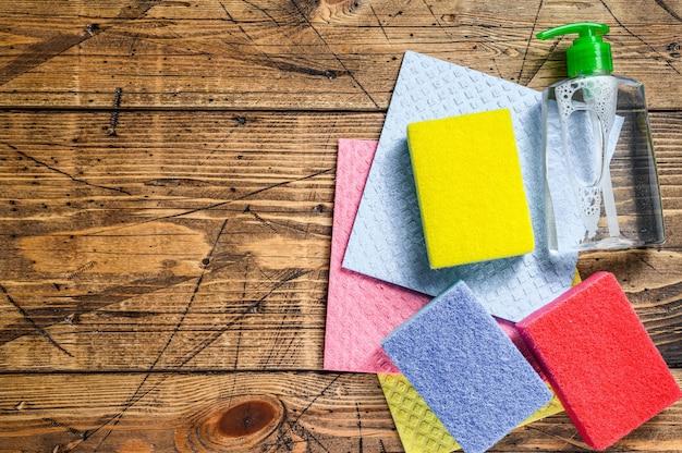 洗濯物や掃除用品、春の大掃除サービスのための国内用品。木製の背景。上面図。スペースをコピーします。