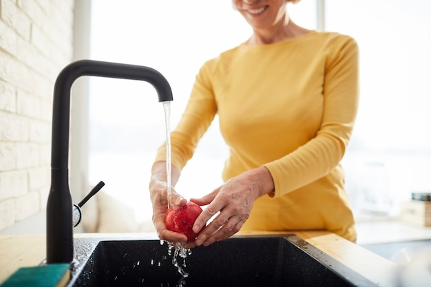 Washing apple under water from tap
