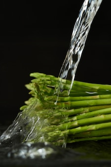 Washing the asparagus with a stream of water, pouring water from the tap on the vegetables close up