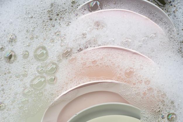 お皿を洗う、台所の流しに浸る道具のクローズアップ。