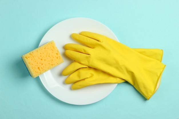 食器洗いのコンセプト。青いパステルカラーの背景にスポンジとゴム手袋でプレート。上面図