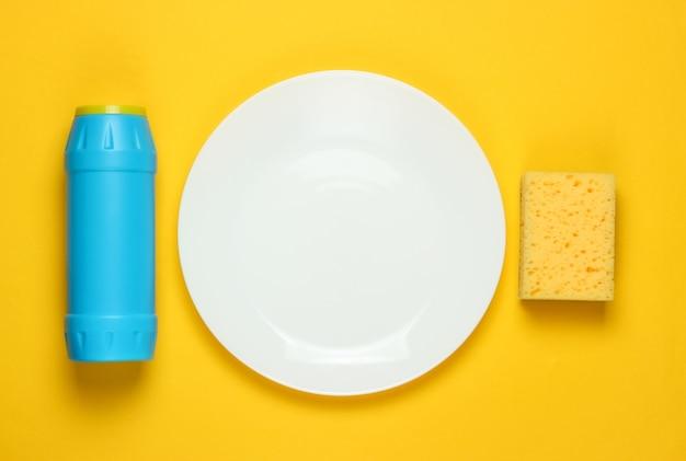 食器洗いのコンセプト。黄色の背景にスポンジ、洗剤のボトルをプレートします。上面図