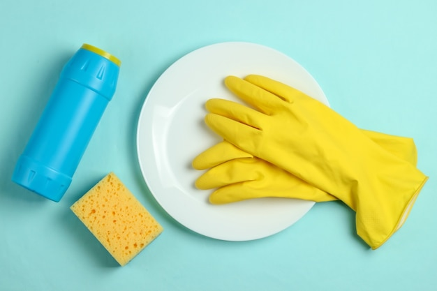 Washing dishes concept. plate with a sponge and rubber gloves, bottle of detergent on a blue pastel background. top view