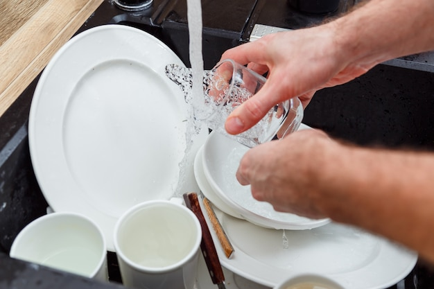 Washing dishes - man hands in gloves rinsing glass under running water in the sink.