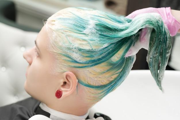 미용실에서 샴푸로 젊은 여성의 에메랄드 머리 색깔 세척