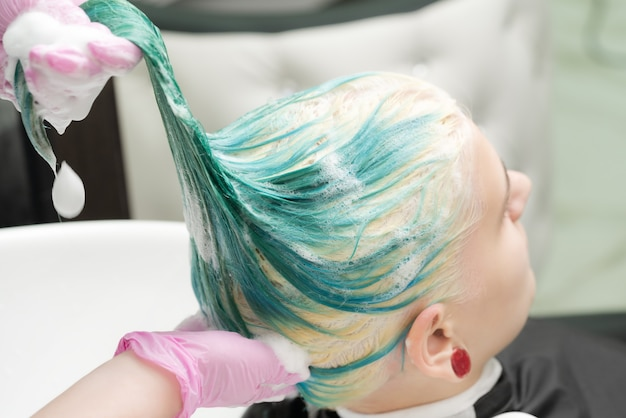 Стирка зеленого цвета волос молодой женщины шампунем в раковине, работая парикмахером в розовых защитных ...