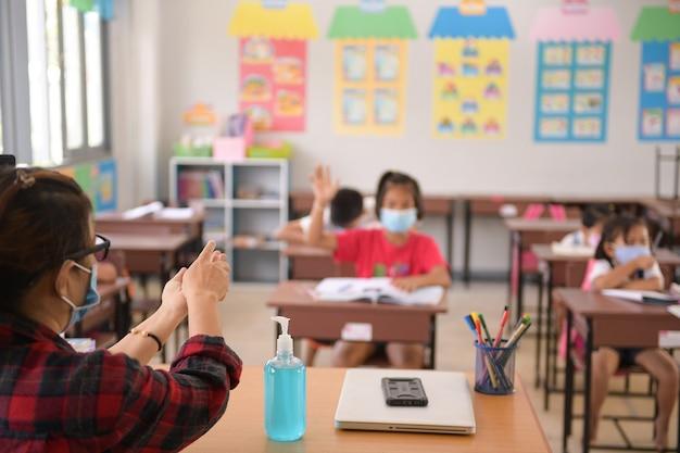 교실에서 코로나 바이러스 (covid-19) 예방을 위해 소독제 젤로 손 씻기 공공 장소의 펌프 병에서 알코올 소독제 또는 알코올 젤로 손을 씻습니다.