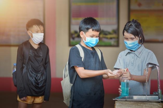 教室でコロナウイルス病covid19を予防するために消毒ジェルで手を洗う