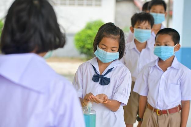 教室でのコロナウイルス病の予防のための消毒剤ゲルによる手を洗う。