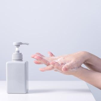 手を洗う。手を洗うために液体石鹸を使用しているアジアの若い女性、灰色の白い背景で分離されたコロナウイルスの拡散を停止するための衛生の概念、クローズアップ。