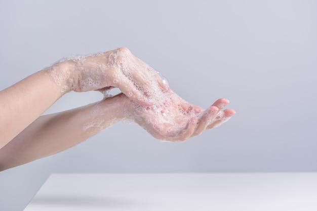 손씻기. 액체 비누를 사용하여 손을 씻는 아시아 젊은 여성, 위생의 개념