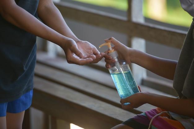 公共エリアでポンプボトルからアルコール消毒剤またはアルコールゲルで手を洗う