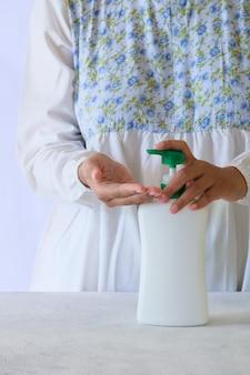 ポンプボトルから液体石鹸またはアルコールジェルで手を洗う。 covid-19コロナウイルスの発生感染の予防と管理。衛生とヘルスケアの概念