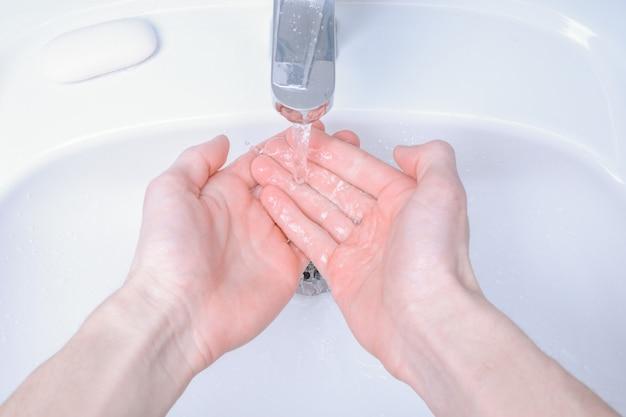 コロナウイルス、covid-19防止、コロナウイルスの拡散を防ぐための衛生のために、石鹸でこすり洗いしているシンクで手を洗います。