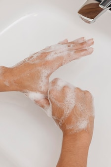 Washing hands rubbing with soap flat lay