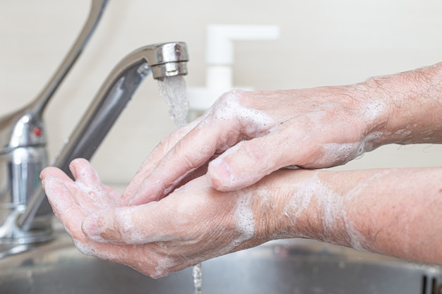 Washing hands rubbing with soap man for corona virus prevention