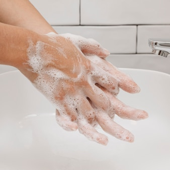 Washing hands rubbing with soap in the sink