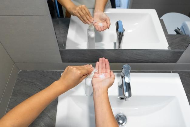 Мытье рук протирая мылом женщине для профилактики вируса короны, гигиены, чтобы остановить распространение коронавируса