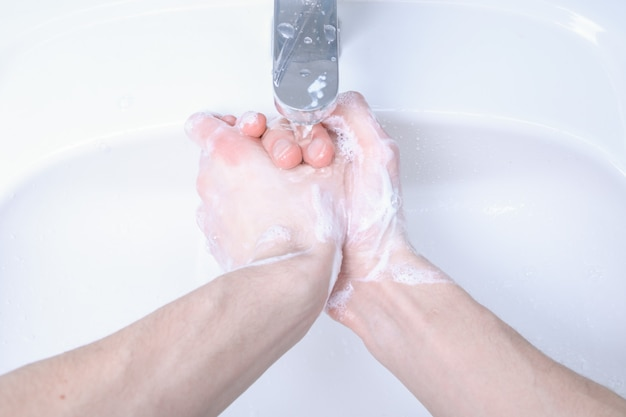 Washing hands in the sink rubbing with soap man for corona virus ,covid-19 prevention, hygiene to stop spreading coronavirus.destruction of the virus