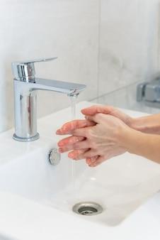 화장실 수돗물 아래서 손 씻기