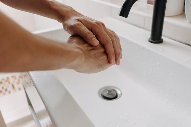 トイレの掃除と保護の概念で泡で手を洗う