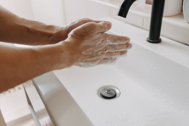 Washing hands with foam in the toilet concept of cleaning and protection