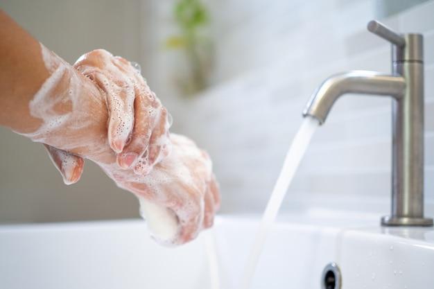 石鹸と水で手を洗います。女性は、洗面台でハンドソープをこすります。世界中の手指衛生と手洗いのコンセプト。細菌やウイルスの蓄積を減らします。
