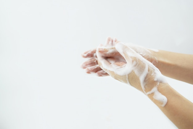 Washing of hands with soap foam.