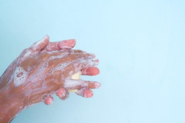 Мытье рук с мылом на синем фоне.