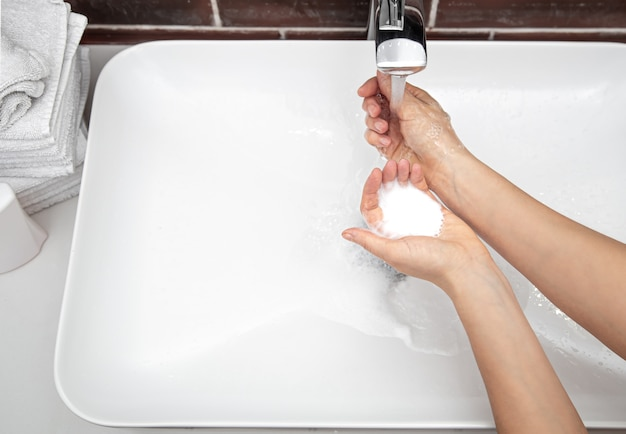 Washing hands with soapy water under running water. concept of personal hygiene and health.