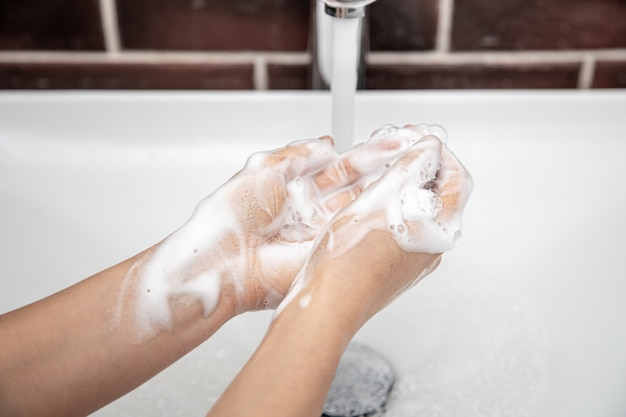 Washing hands with soapy water under running water.  personal hygiene and health.