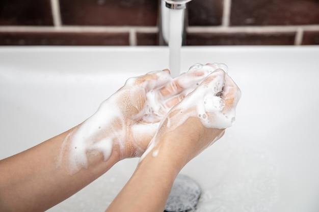 흐르는 물에 비눗물로 손을 씻으십시오. 개인 위생 및 건강.