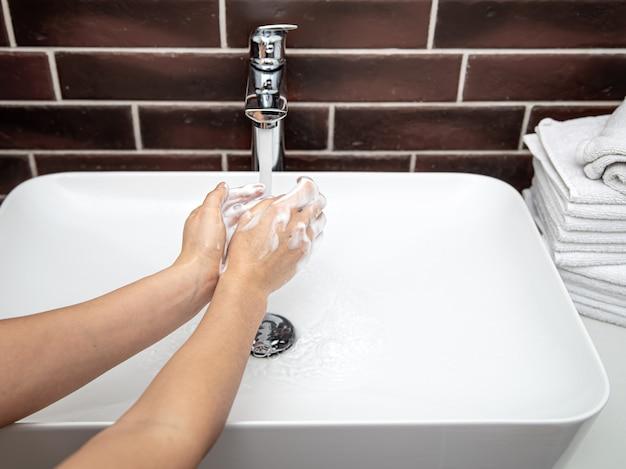 流水の下で石鹸水で手を洗う。個人の衛生と健康の概念。