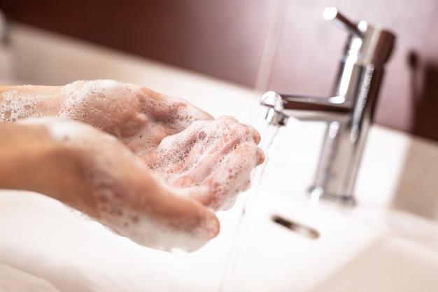 浴室で水と液体石鹸で手を洗う。衛生アンチウイルスの概念。