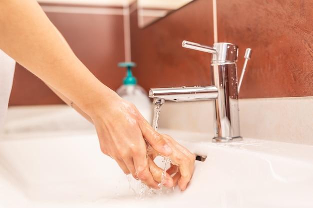 浴室で水と液体石鹸で手を洗う。