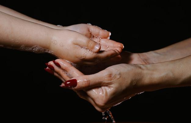 黒の背景に水スプレーで手を洗う。子供と大人の手。