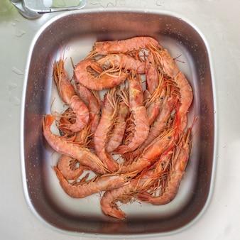Мыть большие свежие креветки в раковине. приготовленные свежие гигантские креветки