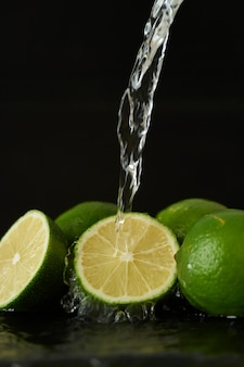 Washing lime with a stream of water, pouring water from the tap on the vegetables