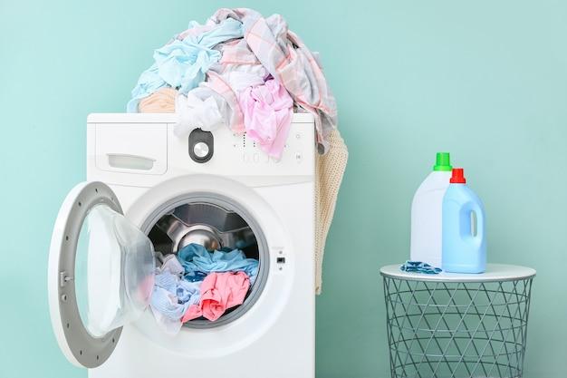 Стиральная машина с грязной одеждой и моющими средствами в домашней прачечной