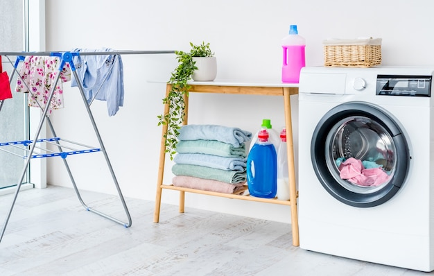 Washing machine with laundry in bathroom and furniture with detergents for cleaning and housework