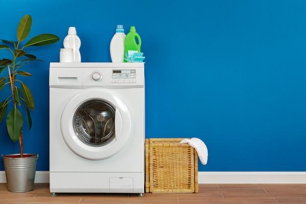 Washing machine with laundry on blue wall background, close up.