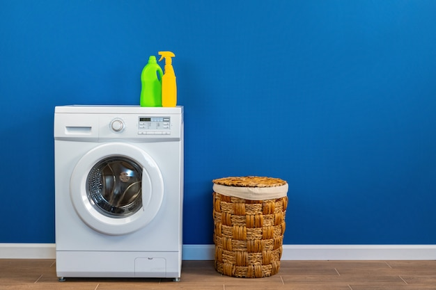 Washing machine with laundry on blue wall