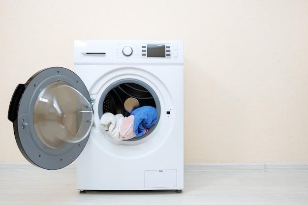 ベージュの壁の近くのドラムの洗濯物と洗濯機