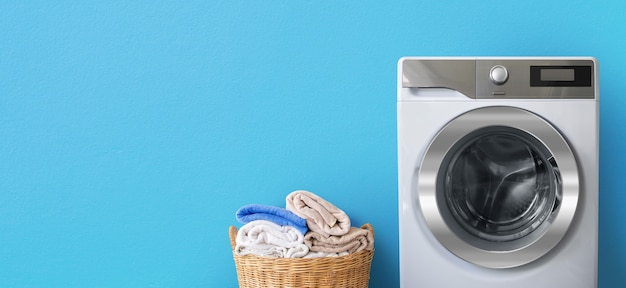 Washing machine with laundry near clean bath towels in wicker basket on blue wall background