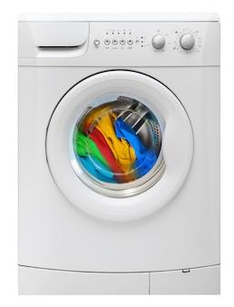 白で隔離された洗濯タンクで回転する色とりどりの服を備えた洗濯機