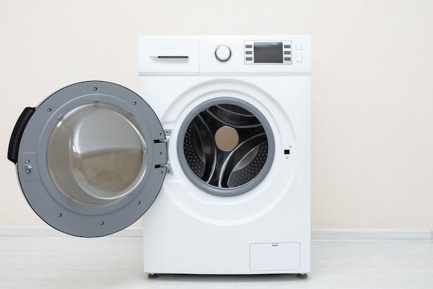 ベージュの壁に対して床に開いたドアが付いている洗濯機