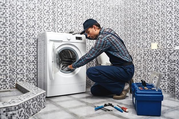 세탁기가 누출되었습니다. 배관공이 세탁기를 수리합니다.