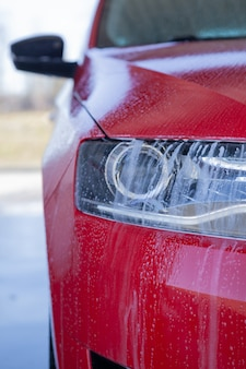Washing a modern car with high-pressure water and soap, cleaning the headlights