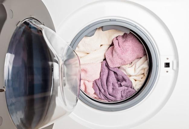 Стиральная или сушильная машина загружена бельем. стирка, концепция весенней уборки